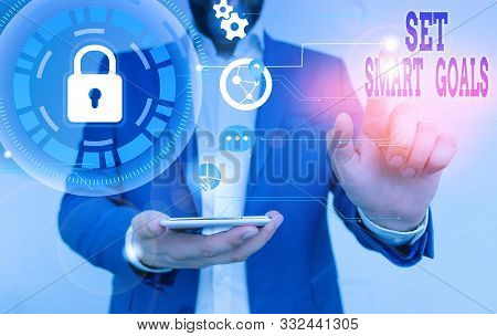 Conceptual hand writing showing Set Smart Goals. Business photo text giving criteria to guide in the setting of objectives Male human wear formal suit presenting using smart device. stock photo