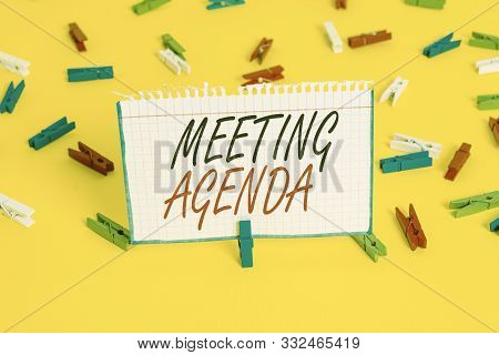 Writing note showing Meeting Agenda. Business photo showcasing items that participants hope to accomplish at a meeting Colored clothespin papers empty reminder yellow floor background office. stock photo