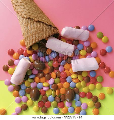Multicolored small candies and waffle horn on a bright two-color background. Candy In Ice Cream Cone. stock photo
