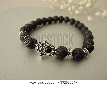 Fashionable bracelets with lava stone and pendants hamsa stock photo