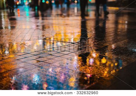 Rainy night in a big city, reflections of lights on the wet road surface. The view from the street level. Pedestrian feet and abstract background. stock photo