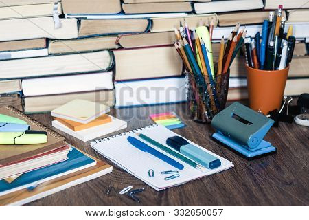 School stationery accessories - notebook, copybook stack with plastic holder pencils, pens, markers, paper clips, stickers, notepads, sharpener with stack of books education concept background stock photo