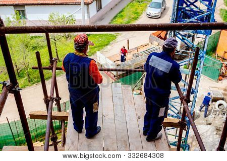 Riggers are standing on scaffold with wooden platform high up on scaffold above construction site. stock photo