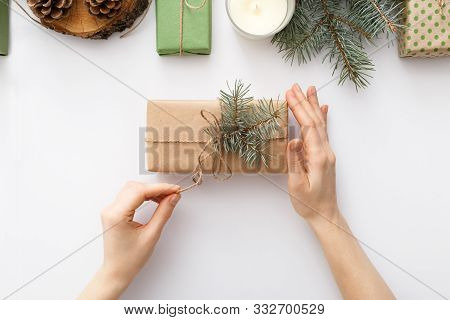 Female Hands Hold A Box With A Christmas Gift On White Table With Christmas Decorations. Christmas,