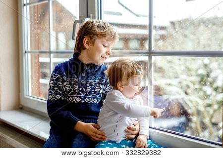 Happy adorable kid boy and cute baby girl sitting near window and looking outside on snow on Christmas day or morning. Smiling children, siblings, little sister and brother looking on winter snowfall. stock photo