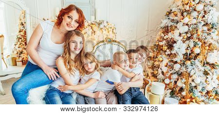 Happy family mother and five children relax playing near Christmas tree on Christmas eve at home. Mom, daughters, sons in light room with winter decoration. New Year time for celebration. Banner stock photo