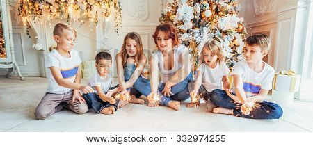 Happy family mother and five children playing sparkler near Christmas tree on Christmas eve at home. Mom, daughters, sons in light room with winter decoration. New Year time for celebration. Banner stock photo