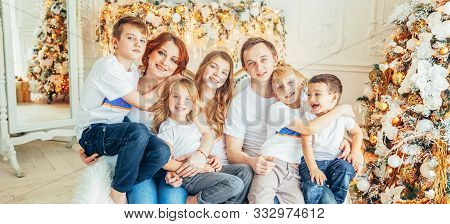 Happy family mother father five children relax playing near Christmas tree on Christmas eve at home. Mom dad daughter son in light room with winter decoration. New Year time for celebration Banner stock photo