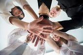 Business individuals stacking so as to demonstrate solidarity hands together