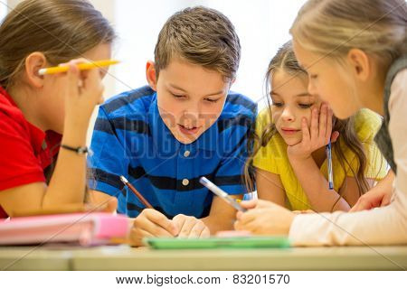 education, elementary school, learning and people concept - group of school kids with pens and papers writing in classroom stock photo