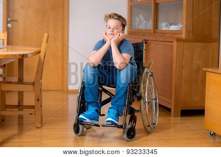disabled boy in wheelchair at home in the living room stock photo