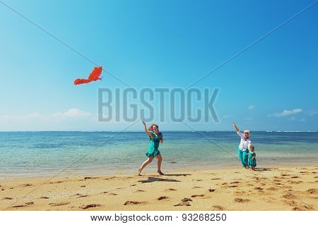 Carefree mother having a fun running with flying red kite on sea beach to baby girl and grandmother. Three generations of family happy parenting and active leisure during summer vacation with child stock photo