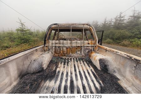 The back open cab of a burnt out pick up truck left abandoned on common ground. stock photo