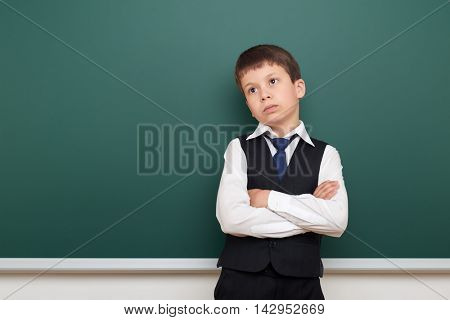 school student boy posing and think at the clean blackboard, grimacing and emotions, dressed in a black suit, education concept, studio photo stock photo