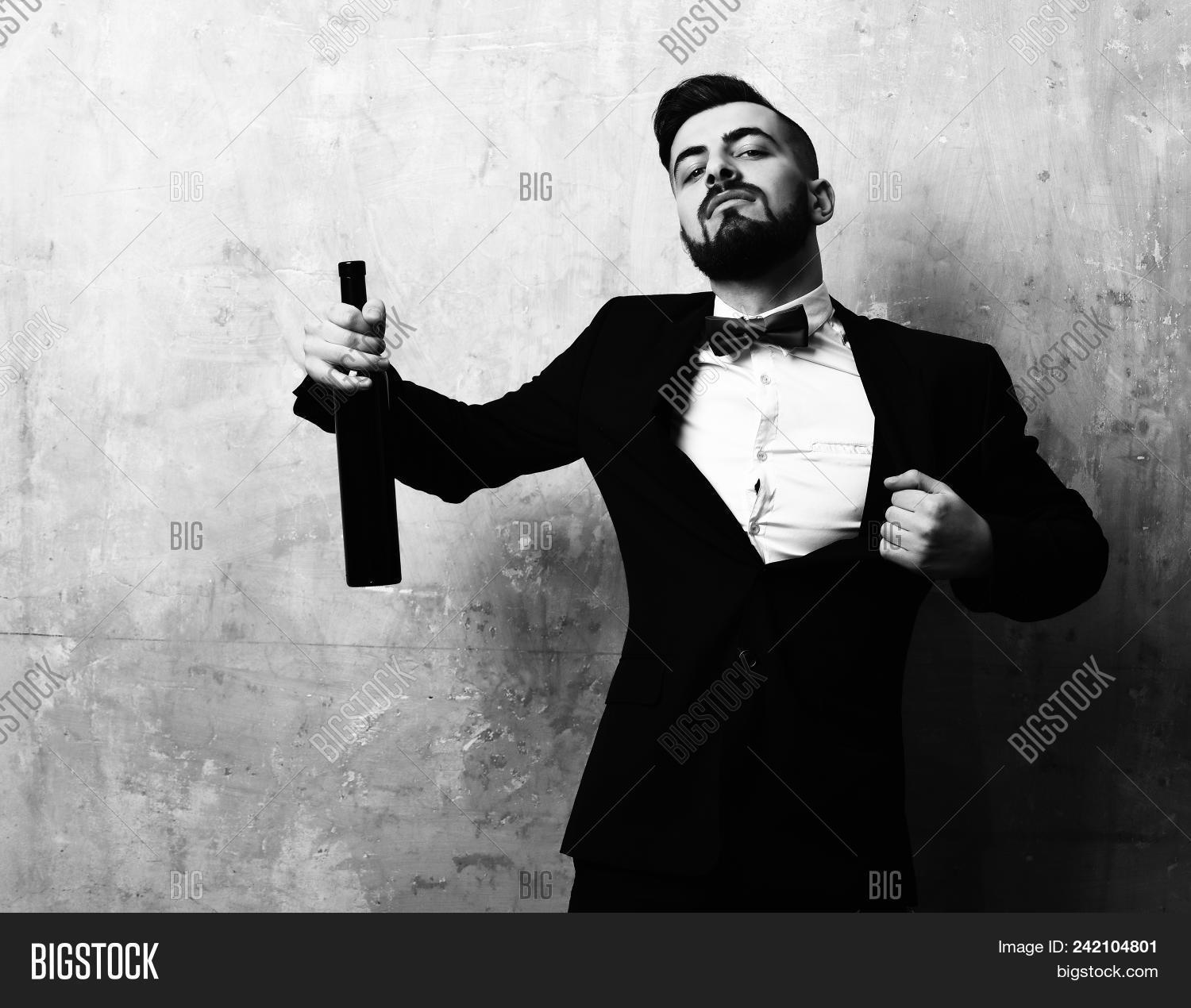 alcohol,alcoholic,background,barbershop,beard,bearded,beige,beverage,black,bottle,bow,businessman,caucasian,classic,classy,concept,drink,elegant,expression,face,familiar,friday,glass,haircut,handsome,leisure,liquid,male,man,moustache,night,old,party,red,relax,spirits,suit,time,unshaved,unshaven,vintage,wall,wine,young