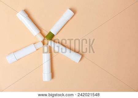 Flat lay composition with hygienic lipsticks on color background stock photo