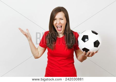Beautiful European young angry screaming woman, football fan or player in red uniform holding soccer ball isolated on white background. Sport, play football, health, healthy lifestyle concept stock photo