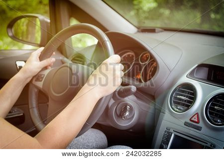 Woman driving a car, close up of her hand at the steering wheel. View from behind stock photo