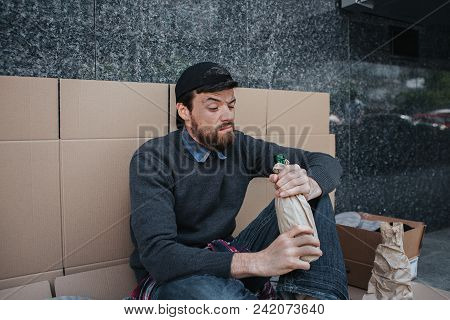 Homeless man is sitting and leaning to the wall with cardboard. He is looking inside the bottle with alcohol stock photo