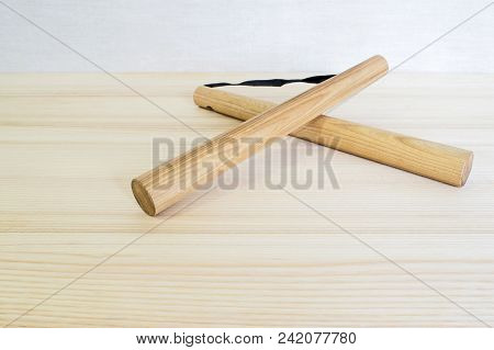 Wooden nunchuck lay on the ash top. stock photo