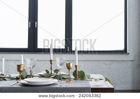 close up view of rustic table arrangement with eucalyptus, vintage tarnished cutlery, candles in candle holders and empty plates stock photo