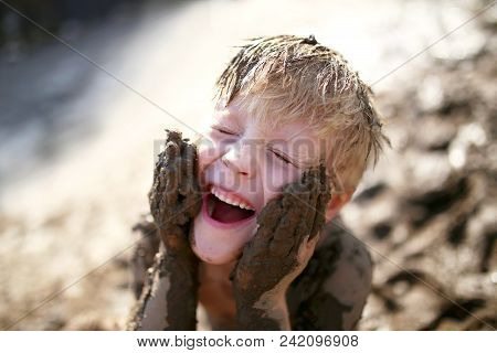 A cute little boy child is laughing as he plays outside in the mud and rubs dirt on his face with his hands. stock photo