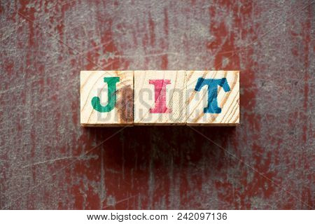 Letter block in word JIT (Abbreviation of just in time) on old red wood background stock photo