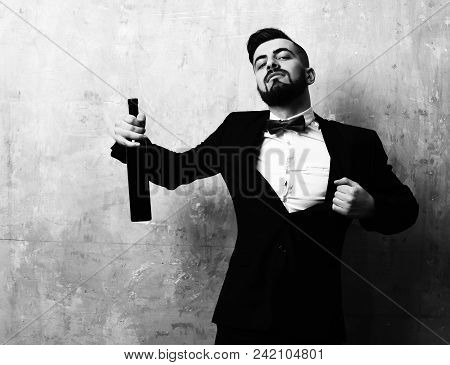 Concept of friday night party and alcoholic beverages: familiar unshaved man with bottle of wine in black suit and red bow on beige background stock photo