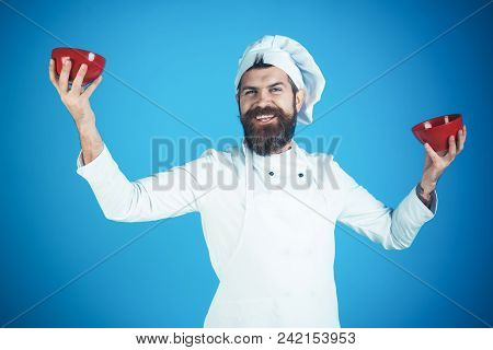 Male chef in white uniform holds red bowls. Bearded chef isolated on bluebackground. Cooking concept. Happy bearded chef shows bowls. stock photo