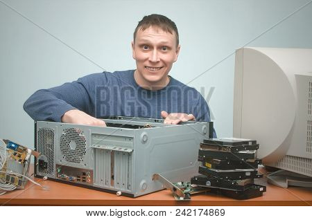 Happy computer repairman fixing a computer hardware. It electronic engineer. stock photo