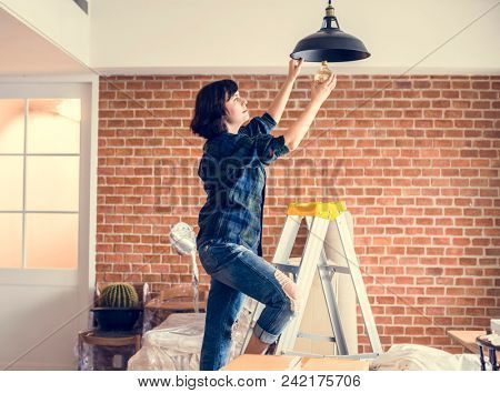 Woman changing lightbulb stock photo