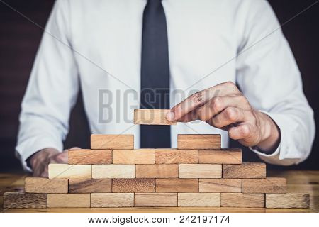 Risk To Make Business Growth Concept With Wooden Blocks, hand of man has piling up and stacking a wooden block, Alternative risk concept, plan and strategy in business. stock photo