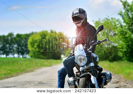 Motorcyclist in helmet and leather jacket sits on his motorcycle outdoors. Motorbike travelling background. stock photo