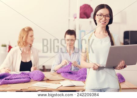 Ready for challenges. Waist up of confident skilled couturier holding a laptop in hands and expressing delight while professional tailors knitting at the table stock photo