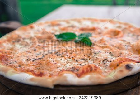 Big Tasty Pizza Margarita on the restaurant wooden table. stock photo