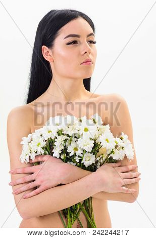 Woman with smooth healthy skin looks attractive. Lady covers breasts with flowers, isolated on white. Girl on calm face naked holds chamomile flowers in front of breasts. Natural cosmetics concept. stock photo