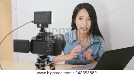 Woman talking in front of the digital camera with her laptop computer for making vlog at home  stock photo