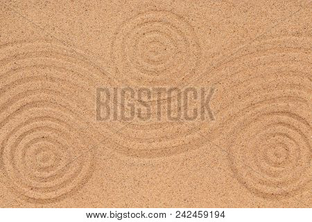Three concentric circle and wave lines on the sand. Texture of sand. View from above stock photo