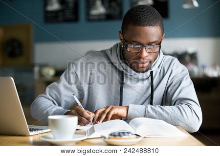 Focused Millennial African American Student In Glasses Making Notes Writing Down Information From Bo