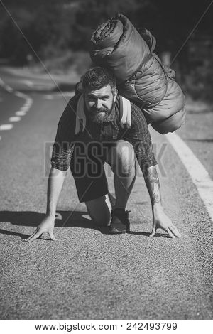 Man looking at camera. Handsome man face. Man traveler smile with backpack on start position to run on road. Health and active lifestyle. Ready steady go. Summer vacation, travel concept. stock photo