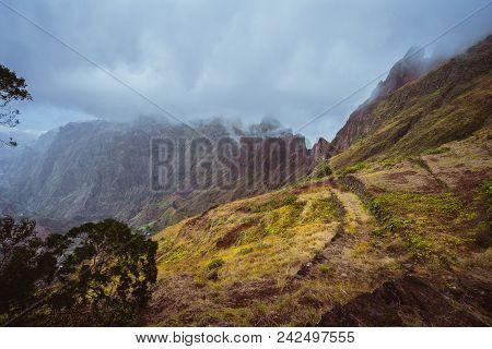 Trekking path along the mountain edge overgrown with verdant grass. Mountain peaks are covered by fog . Xo-Xo Valley. Santo Antao Island, Cape Verde Cabo Verde. stock photo