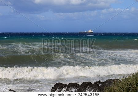 Large Container Ship Near Coastline in Windy Day: Stormy Weather. stock photo