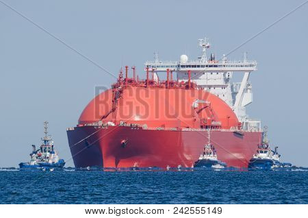 LNG TANKER - The red ship enters port with assurance of tugs stock photo