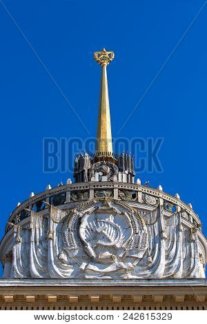retro bas relief with a hammer and sickle of the ussr at the top of the facade of the building with a star on the stele. stock photo