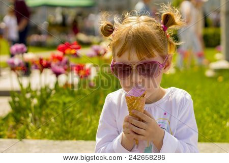 The girl in fashion glasses is eating ice cream. Child and delicious ice cream. Face smeared in ice cream stock photo