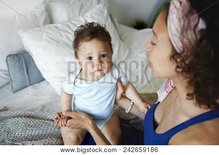 Picture of happy Hispanic mom in casual wear nursing her baby child in bedroom, holding him on her lap. Sweet portrait of adorable toddler spending morning with mother at home. Selective focus stock photo