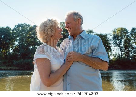 Low-angle side view portrait of a romantic senior couple in love enjoying a healthy and active lifestyle outdoors in summer stock photo