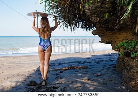 Sporty girl in bikini with surf board walk along dark sea cliff. Young surfer woman run by black sand beach. Active people in sports adventure camp, extreme water activity on summer family vacation stock photo