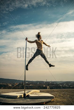 Sexy macho man fly on sky background. Pole dance sport. Strong man dancer workout on pole. Athletic guy make acrobatic elements on pylon. Young man dancing on pylon. Towards the healthier lifestyle stock photo
