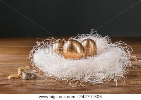 Golden eggs in nest and coins on wooden table. Pension planning stock photo